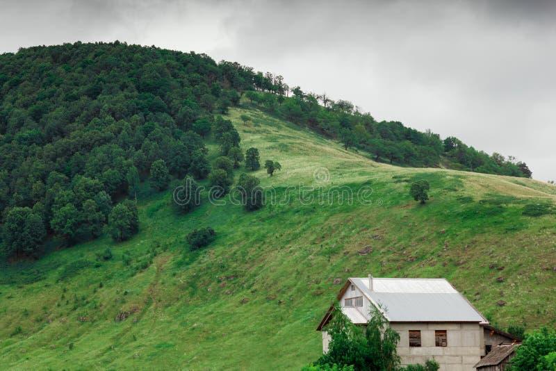 Eenzaam huis op de heuvel dichtbij groen bergbos royalty-vrije stock afbeeldingen