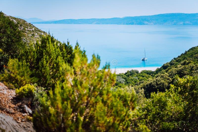 Eenzaam jacht op verborgen Fteri-strandlagune, Kefalonia, Griekenland Ontworpen mening tussen de takken van de pijnboomboom tijde royalty-vrije stock foto's