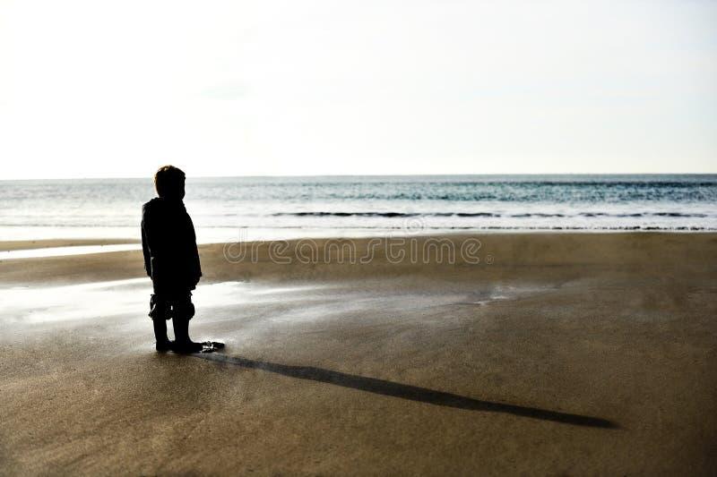 Eenzaam kind op een strand vóór zonsondergang royalty-vrije stock foto
