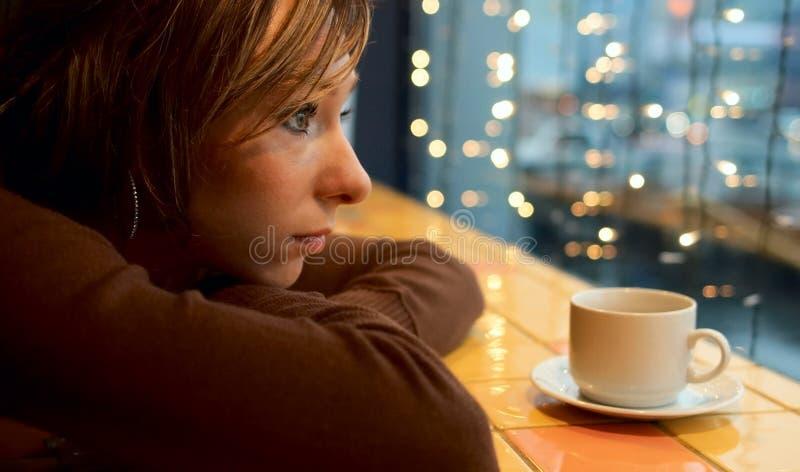 Eenzaam meisje in koffie stock afbeelding
