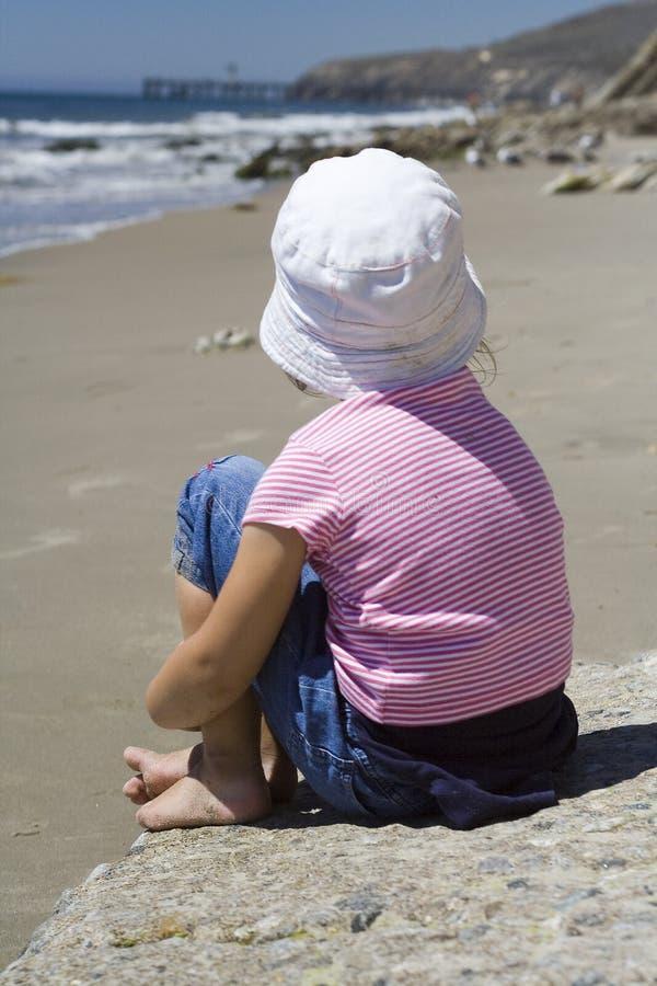 Eenzaam meisje op het strand stock fotografie