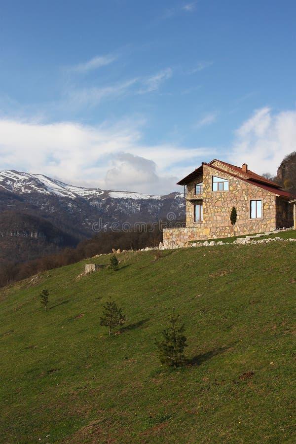 Eenzaam steenhuis op de heuvel op de achtergrond van verticale sneeuwbergen, royalty-vrije stock afbeelding