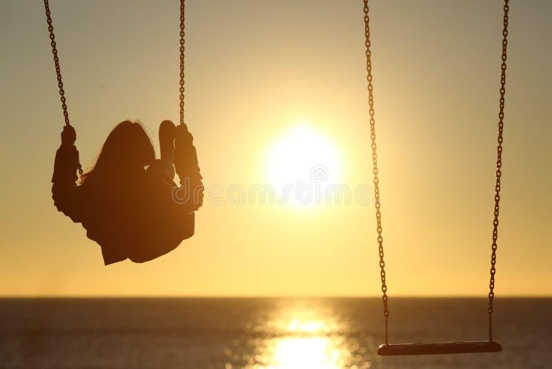 Eenzaam vrouwensilhouet die bij zonsondergang op het strand slingeren royalty-vrije stock fotografie