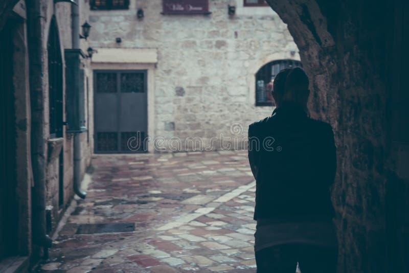 Eenzaam vrouwensilhouet die door donkere tunnel van straat in regenachtige dag in oude stad tijdens regen met exemplaarruimte lop royalty-vrije stock afbeelding