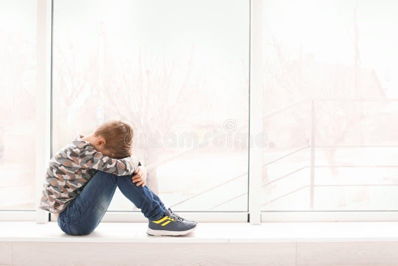 Eenzaam weinig jongen dichtbij het autisme van het venster binnen Kind royalty-vrije stock foto