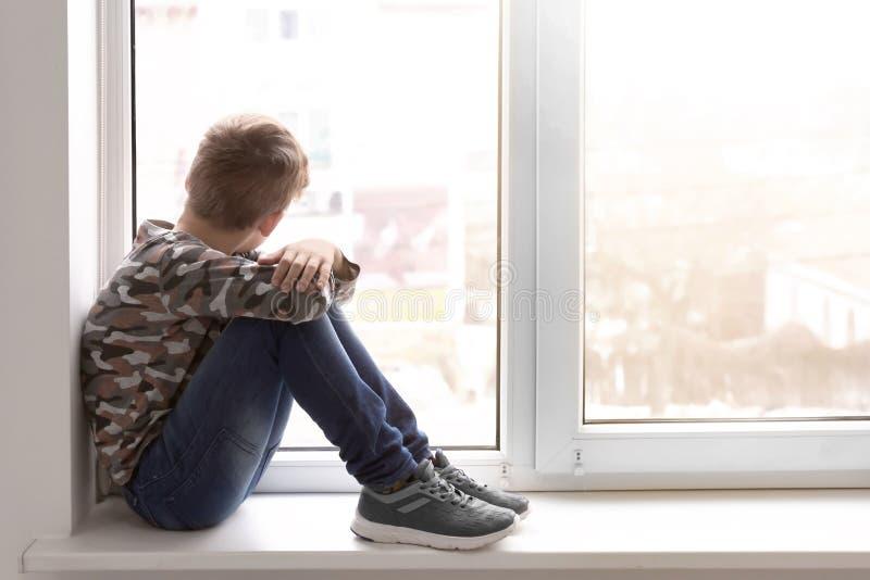Eenzaam weinig jongen dichtbij venster binnen royalty-vrije stock foto