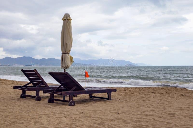 Eenzaam zandig strand met ligstoelen en paraplu's dichtbij het overzees royalty-vrije stock fotografie