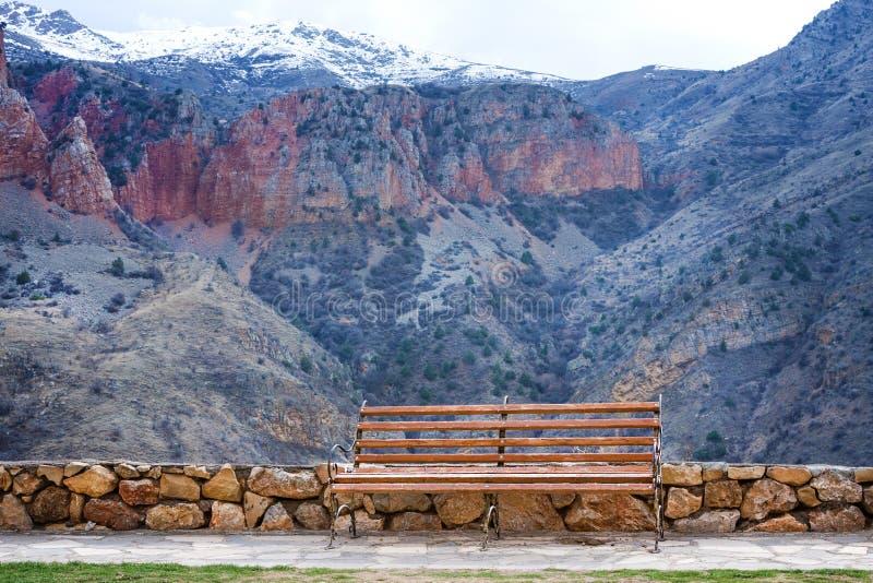 Eenzame bank bij grondgebied van Middeleeuws Armeens Noravank-klooster complex tegen rode bergen, Armenië stock foto's
