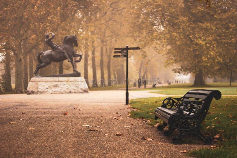 Eenzame bank naast Fysiek Energiestandbeeld in Hydepark droefheid, melancholie, mistroostigheid, eenzaamheid royalty-vrije stock afbeeldingen