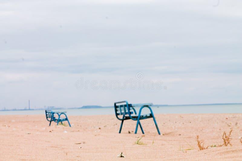Eenzame banken in een verlaten dorp in het gebied van de vijandelijkheden in Oekraïne Aanzicht van de Zee van Azov tot Mariupol R stock foto
