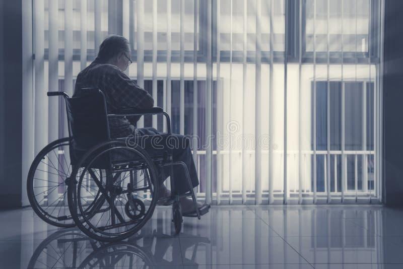 Eenzame bejaardezitting op rolstoel stock foto's