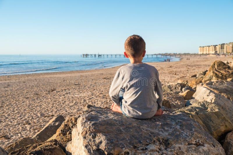 Eenzame blootvoetse jongenszitting op de rots stock afbeelding