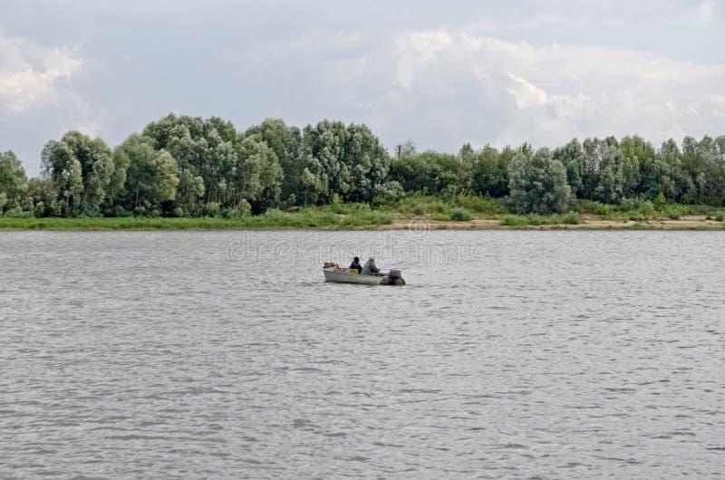 Eenzame boot in het midden van de rivier stock fotografie