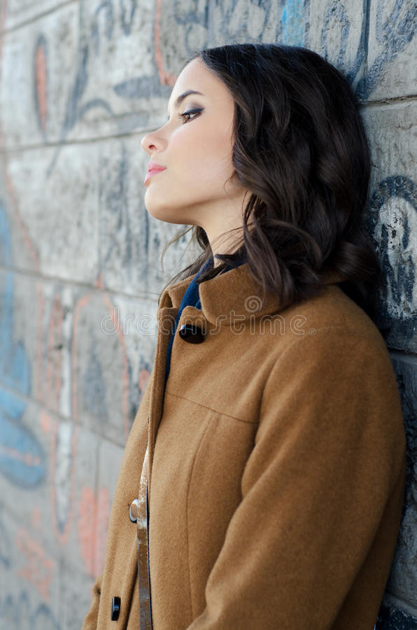 Eenzame dame die op de graffitimuur leunen in stedelijk milieu royalty-vrije stock foto's