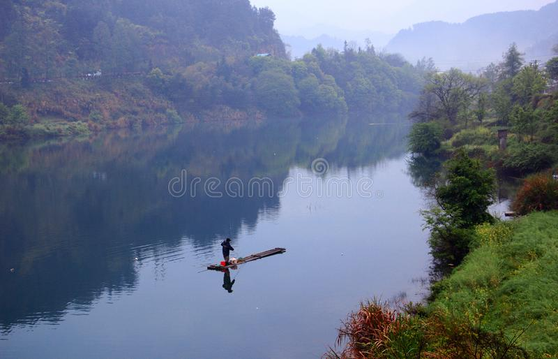 Eenzame die bamboevlotten op het kalme meer worden gedreven royalty-vrije stock afbeeldingen
