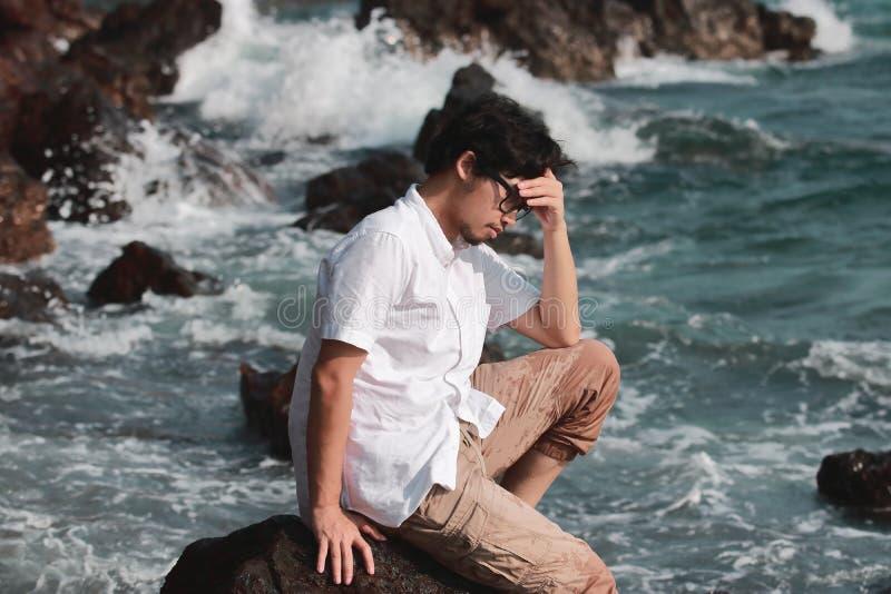 Eenzame droevige jonge Aziatische mens die probleem hebben en op de turkooise kust schreeuwen stock foto