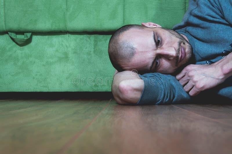 Eenzame en gedeprimeerde mens die op de vloer van zijn huis liggen Hij mist iemand stock afbeelding