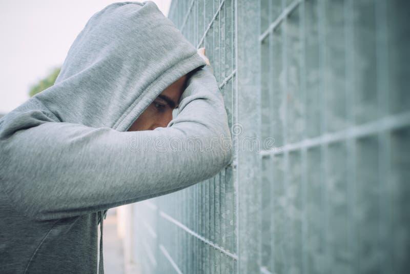 Eenzame en gedeprimeerde Mens die tegen een Omheining leunen stock foto's