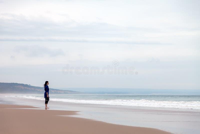 Eenzame en gedeprimeerde vrouw die op het overzees letten stock fotografie