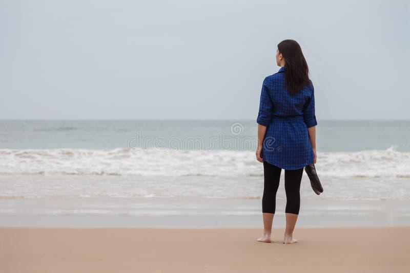 Eenzame en gedeprimeerde vrouw die zich voor het overzees bevinden stock afbeeldingen