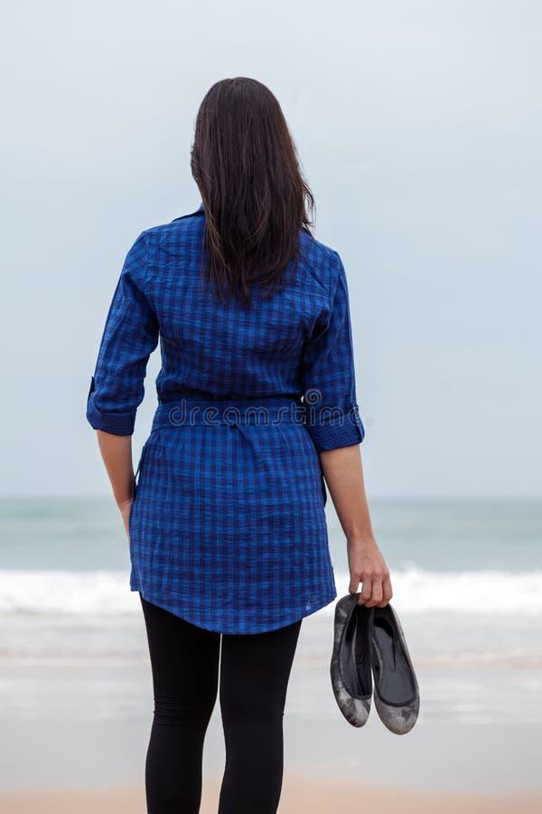 Eenzame en gedeprimeerde vrouw die zich voor het overzees bevinden royalty-vrije stock foto