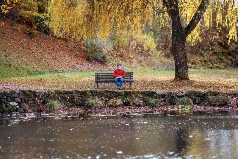 Eenzame hogere mensenzitting op bank door meer in aard, die camera bekijken royalty-vrije stock foto