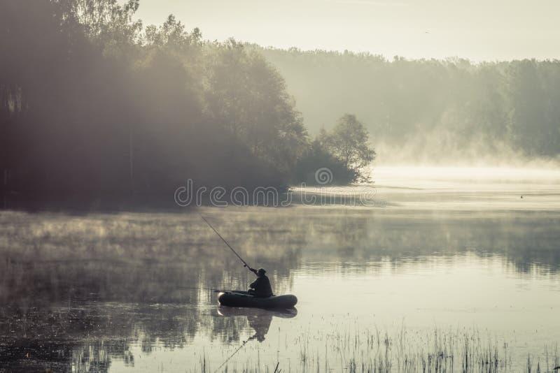Eenzame hogere visser met een hengel op een opblaasbare boot die op het meer vissen stock foto