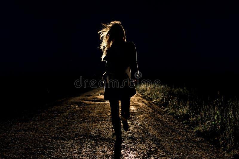 Eenzame jonge bang gemaakte vrouw op looppas van een de lege nachtweg weg in het licht van de koplampen van haar auto stock afbeelding