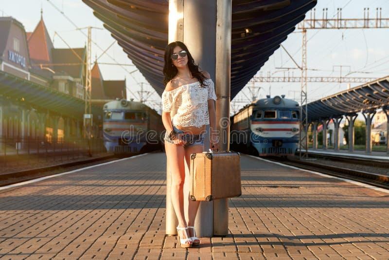 Eenzame jonge donkerbruine vrouw in sexy borrels met oude koffer  stock foto
