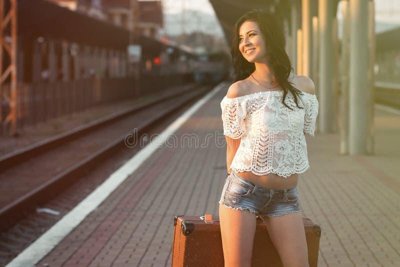 Eenzame jonge donkerbruine vrouw, in sexy borrels met oude koffer  royalty-vrije stock afbeeldingen