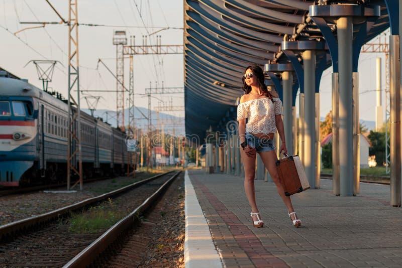 Eenzame jonge donkerbruine vrouw in sexy borrels met oude koffer  royalty-vrije stock foto