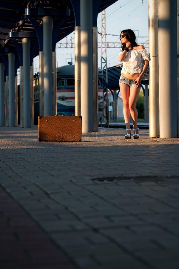 Eenzame jonge donkerbruine vrouw, in sexy borrels met oude koffer  stock foto's
