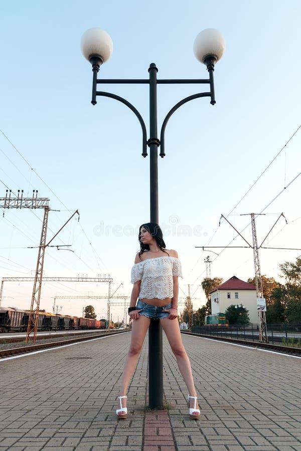 Eenzame jonge donkerbruine vrouw in sexy borrels op postplatform r royalty-vrije stock foto's