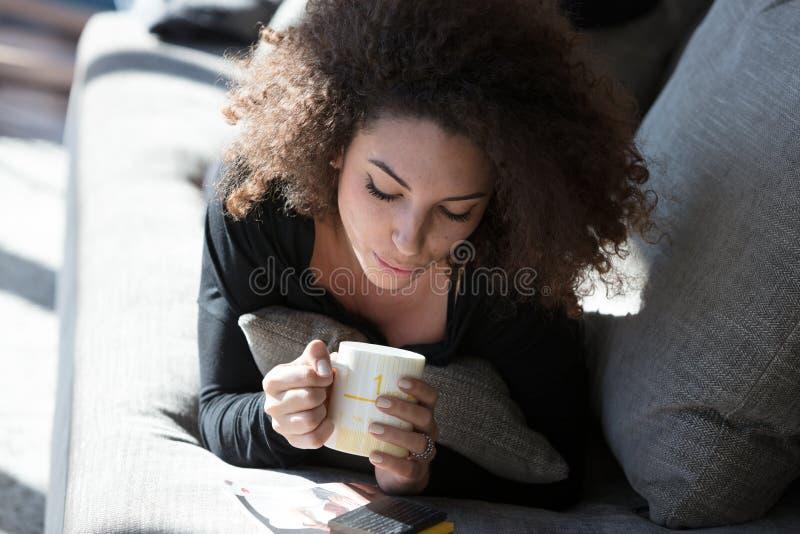 Eenzame jonge vrouw die van een mok koffie genieten royalty-vrije stock afbeeldingen