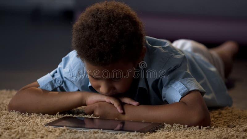 Eenzame jongen het letten op tabletfilm die op vloer thuis liggen, gebrek aan mededeling royalty-vrije stock afbeelding