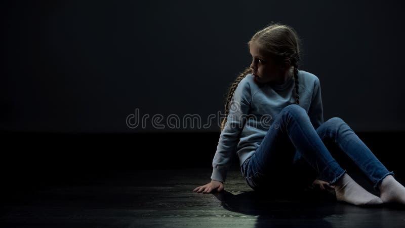 Eenzame meisjeszitting in donkere ruimte en rond het kijken, wees wachtende familie stock afbeeldingen