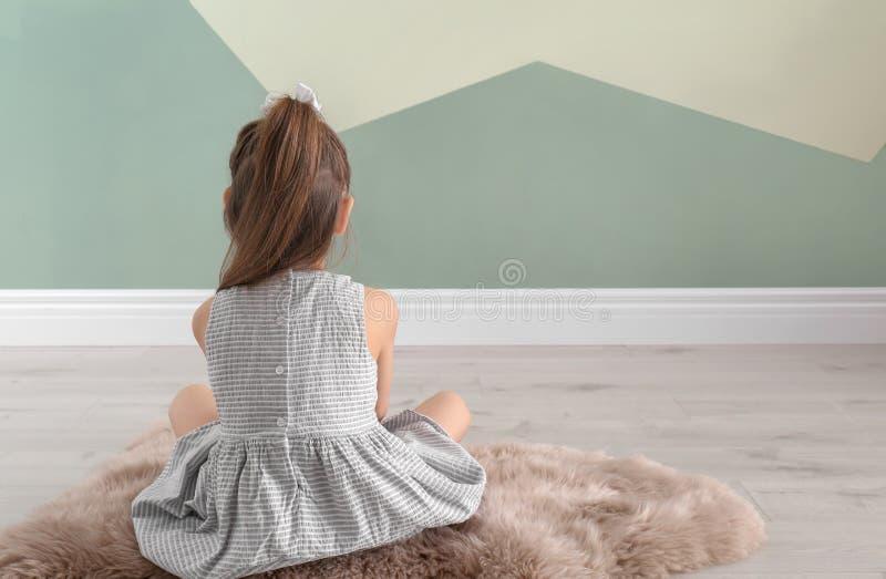 Eenzame meisjezitting op vloer binnen royalty-vrije stock afbeelding