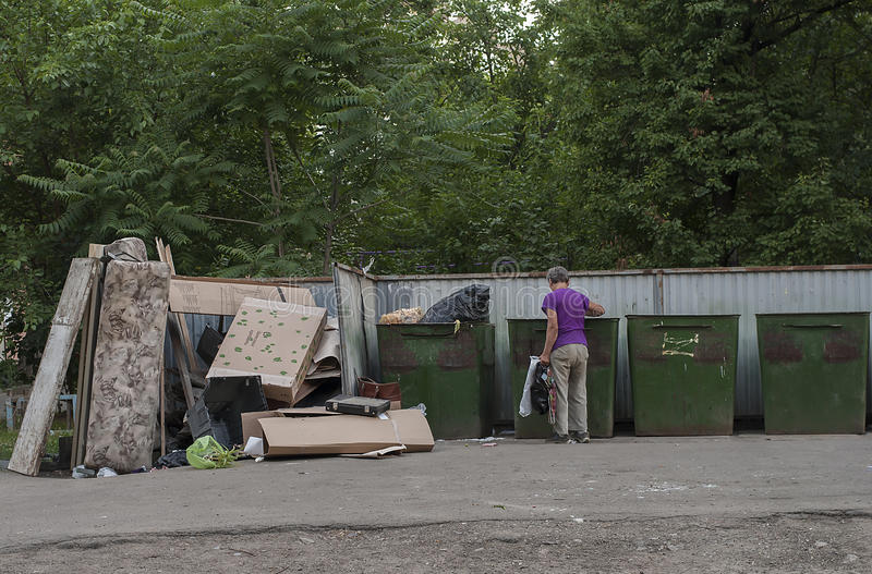 Eenzame mens die in een dumpster doorzoeken stock foto