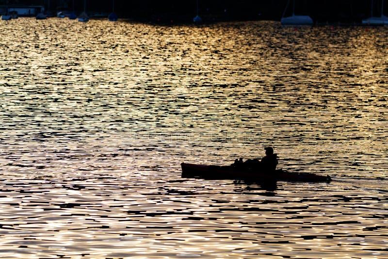 Eenzame mens in kajak als silhouet bij royalty-vrije stock foto