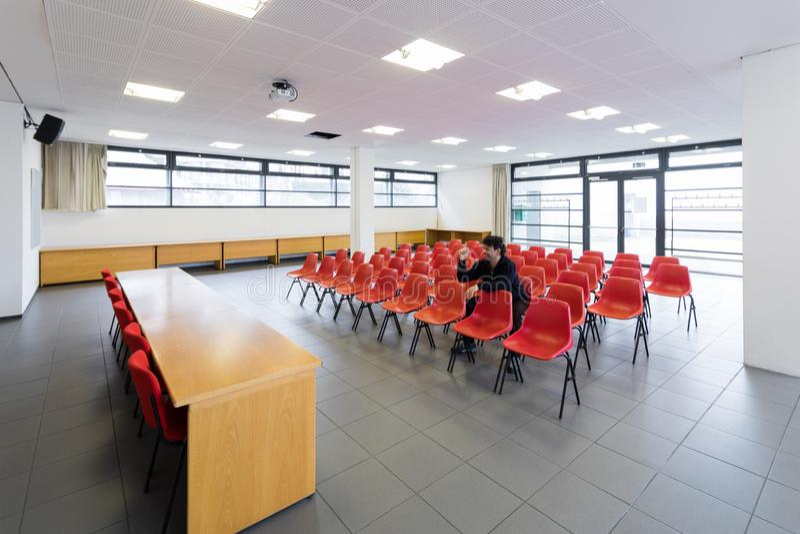 Eenzame mens in lege conferentieruimte, concept royalty-vrije stock afbeelding