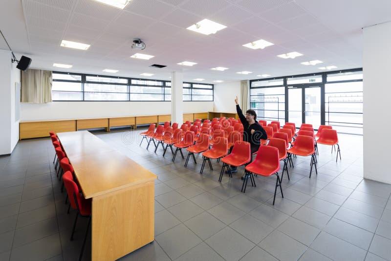 Eenzame mens in lege conferentieruimte, concept stock fotografie