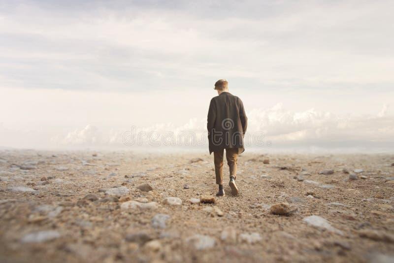 Eenzame mensengangen naar een onbekende bestemming in een woestijn stock foto