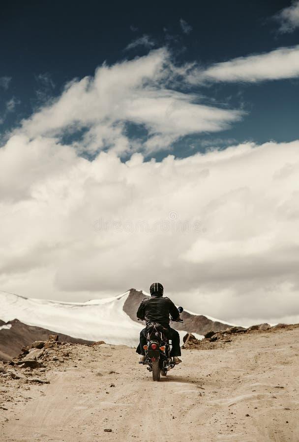 Eenzame motocyclistreiziger op berg rosad in Himalayagebergte stock foto's
