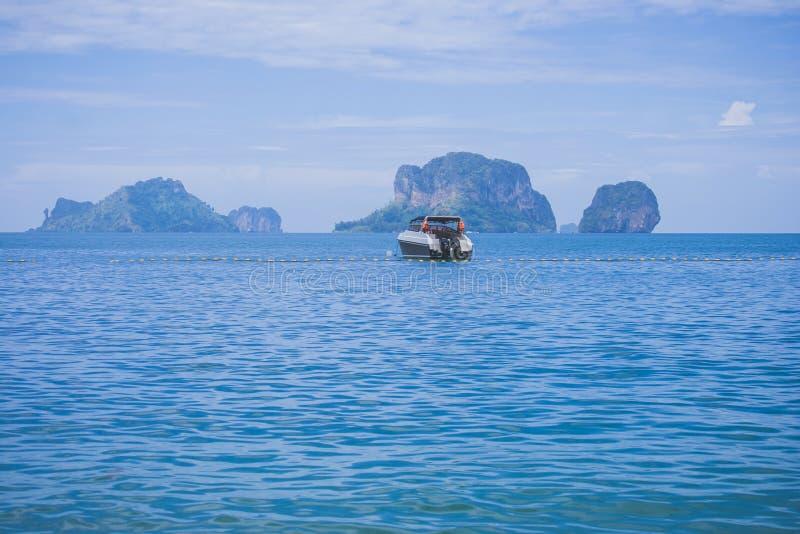 Eenzame motorboot of motorboot die in de oceaan met eiland op de achtergrond drijven stock afbeelding
