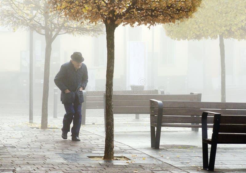 Eenzame oude mens die alleen in het park in de mist lopen