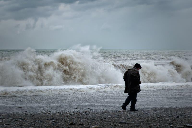Eenzame oude mens die langs kust, achtermening lopen stock afbeeldingen