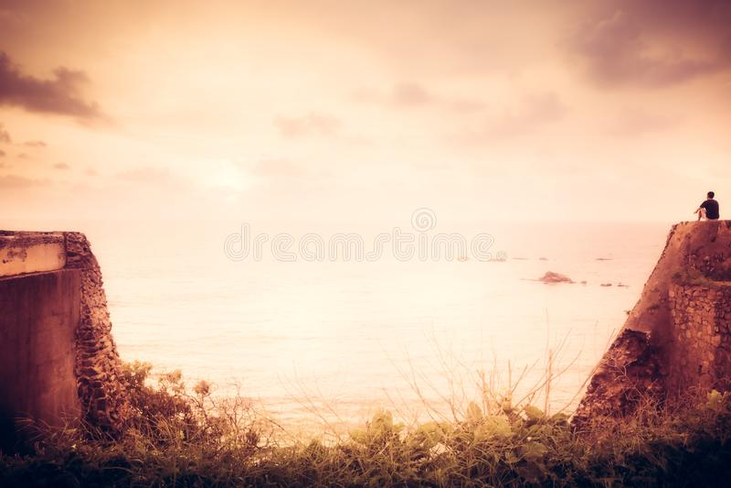 Eenzame reizigersmens die op klip met inspiratie naar horizon met zonlicht tijdens zonsondergang met effect van licht aan het ein stock afbeelding