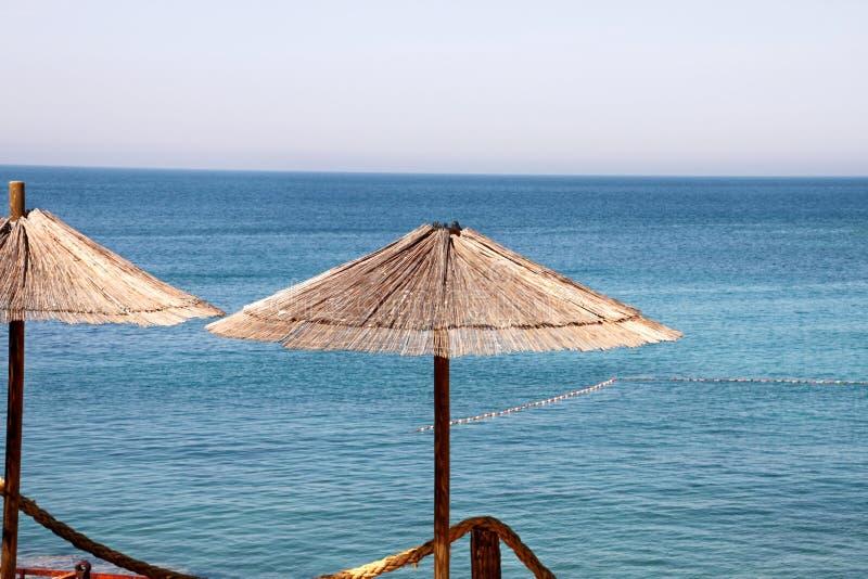 Eenzame rieten zonparaplu bij mediterraan strand door overzees Natuurlijk bamboe sunshades en de parasol van de de zomerparaplu o royalty-vrije stock afbeeldingen