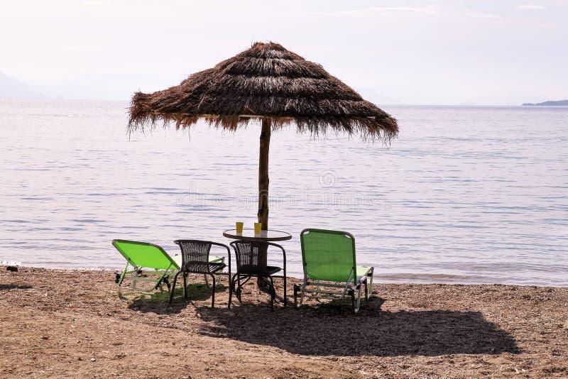 Eenzame rieten zonparaplu bij strand door overzees Natuurlijk bamboe sunshades, de parasol van de de zomerparaplu, ligstoelen, li stock foto