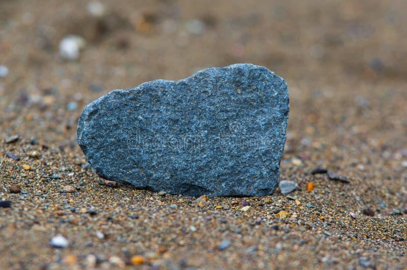 Eenzame steen over rivierzand stock fotografie